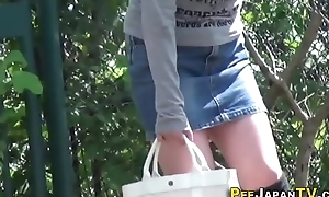 Asian babe peeing outdoor
